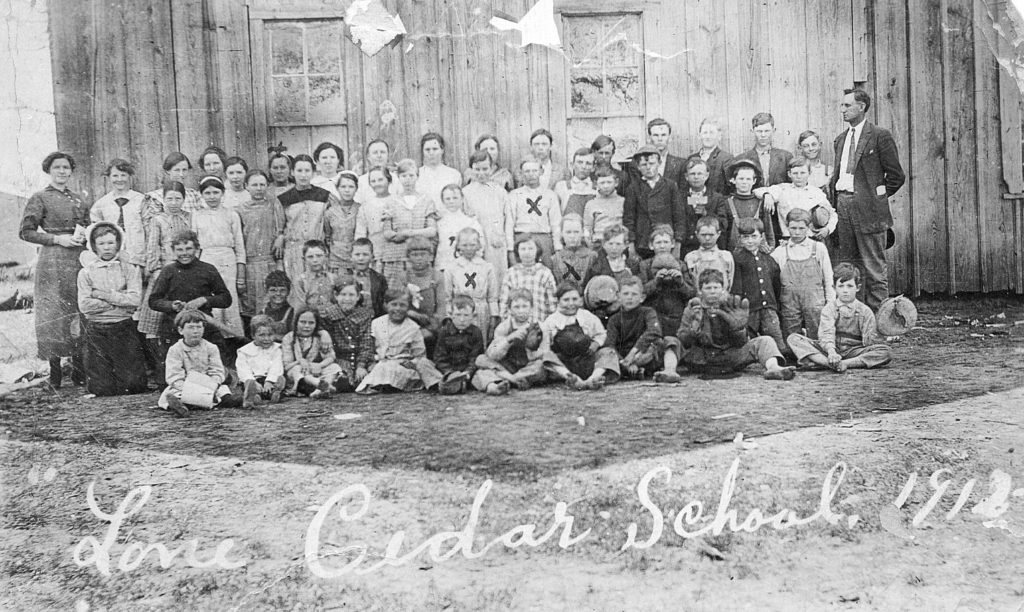 "An old photo marked "" Lone Cedar School"" and a year date that appears to read, 1912. There are four children that have ""X"" marks on or over them. On the back of the photo is written, ""Unknown, Evie, J.D., Myrtle"". These would be Evie Walker (Loosier) my grand-aunt ... J.D. Walker, my grand-uncle, and, Myrtle Walker (Smithen) my grandmother.   (Photograph provided by and in the collection of Johnny Taylor, Marshall, TX, 2017)"